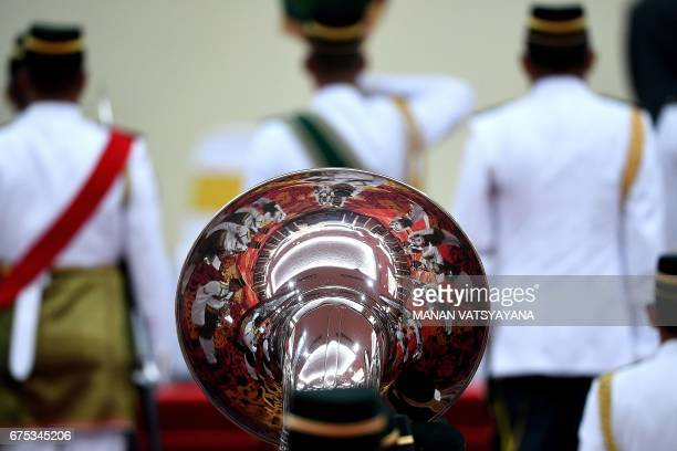 TOPSHOT Royal Malay Regiment honour guards are seen reflected in the marching band's sousaphone during a welcoming ceremony for Bahrain King Hamad...