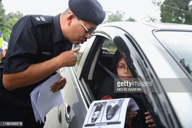 A Royal Malaysian Police officer hands a poster to a motorist bearing a portrait of the missing 15yearold FrancoIrish girl Nora Quoirin during a...