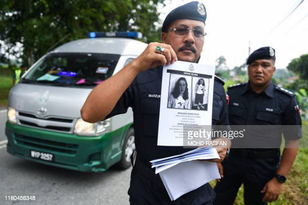 A Royal Malaysian Police officer holds a leaflet bearing a portrait of the missing 15yearold FrancoIrish girl Nora Quoirin at a checkpoint during a...