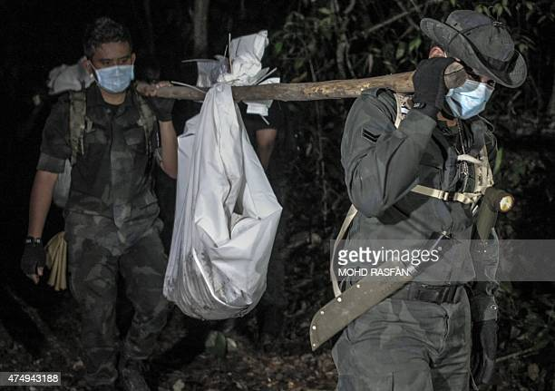 Royal Malaysian Police personnel carry exhumed human remains recovered from the jungle in the Malaysian northern state of Perlis which borders...