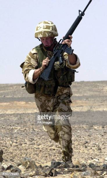 A Royal Marine from the Brigade Recce Force runs to a new fire position whilst reloading his M16 assault rifle during a live firing exercise in the...