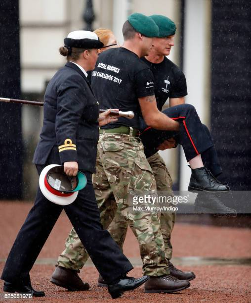 A Royal Marine is carried away after collapsing during the The Captain General's Parade to mark the finale of the 1664 Global Challenge at Buckingham...