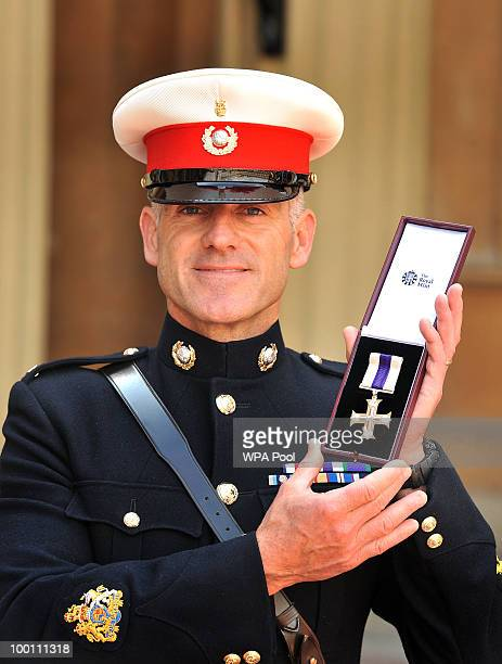 Royal Marine Warrant Officer Class 1 Matthew Tomlinson, with his son Daniel, age 5, poses with his medal after being awarded the Military Cross by...