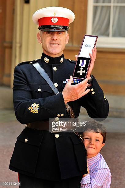 Royal Marine Warrant Officer Class 1 Matthew Tomlinson with his son Daniel age 5 poses with his medal after being awarded the Military Cross by...