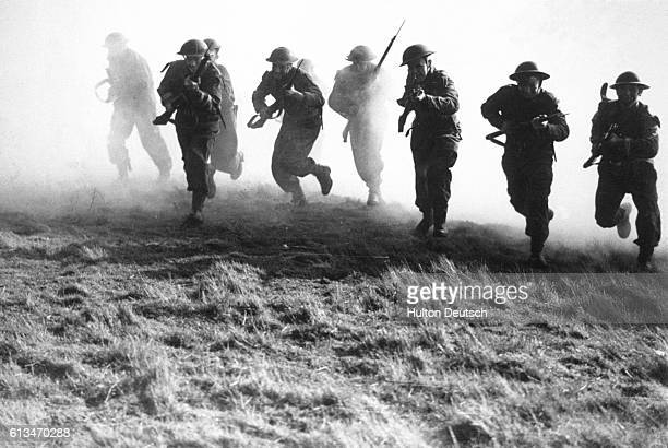 Royal Marines charge through a smoke screen during practice for a land assault in 1944