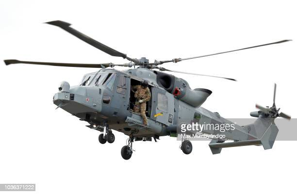 A Royal Marines Commando hangs out of the open door of a Royal Navy Wildcat Maritime Attack Helicopter as it arrives at The Royal Marines Commando...