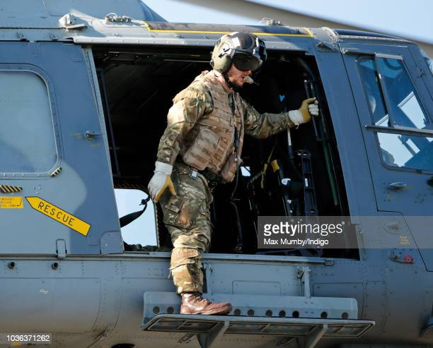 A Royal Marines Commando hangs out of the open door of a Royal Navy Wildcat Maritime Attack Helicopter as it departs The Royal Marines Commando...
