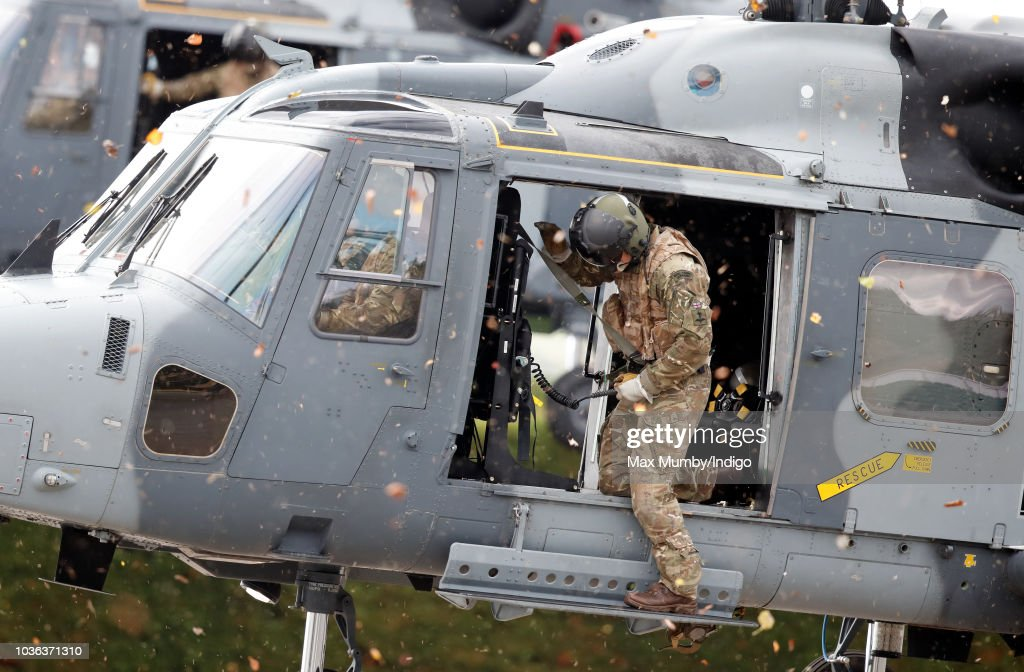 A Royal Marines Commando hangs out of the open door of a Royal Navy Wildcat Maritime Attack Helicopter as it arrives at The Royal Marines Commando Training Centre to transport Prince Harry, Duke of Sussex following a visit on September 13, 2018 in Lympstone, England. The Duke arrived at the centre in a Royal Navy Wildcat Maritime Attack Helicopter for his first visit in his role as Captain General Royal Marines. He met with new recruits undergoing training as well as the Invictus Games Racing Team.