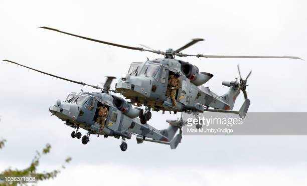 Royal Marines Commandos hang out of the open doors of two Royal Navy Wildcat Maritime Attack Helicopters as they arrive at The Royal Marines Commando...