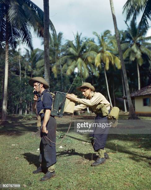 Royal Marines Davies and Bamforth Royal Navy commando infantrymen operate a portable radio telephone set during jungle training in Ceylon prior to...