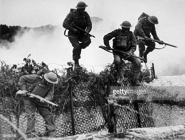 Royal Marines negotiating a barbed wire trench during training on the South Coast