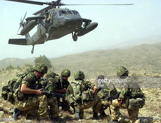Royal Marines of Whisky company 45 commando prepare to board a US Army Black Hawk helicopter during vehicle stops and searches on June 26 2002 near...