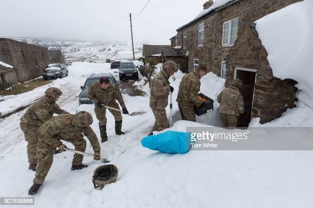 Royal Marines shovel snow after arriving by RAF Chinook to deliver aid to communities cut off by the snow in Cumbria on March 5 2018 in Nenthead...