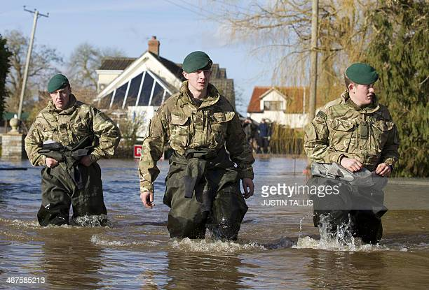 Royal Marines wade through flood waters in Moorland, 19 Kms northeast of Taunton on February 7, 2014. Britain deployed Royal Marines to help with...