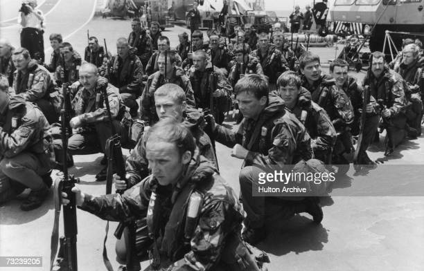 Royal Marines waiting on the flight deck of HMS Hermes for Sea King helicopters to take them on training manoeuvres April 1982