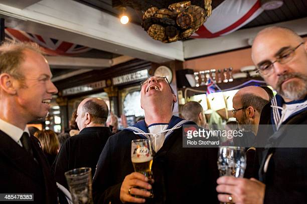 Royal Navel reservists from HMS President laugh during the annual hanging of a hot cross bun at the Widow's Son pub in BromleybyBow on April 18 2014...