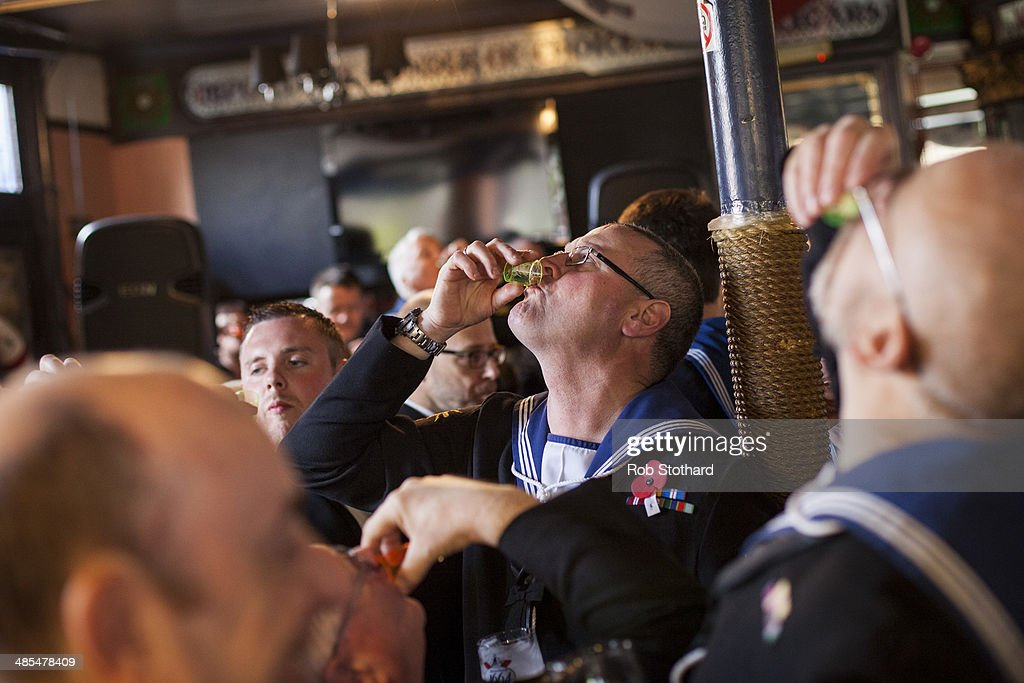 A Royal Navel reservists from HMS President raise a toast to the armed forces in the Widow's Son pub in Bromley-by-Bow on April 18, 2014 in London, England. The Widow's Son was built in 1848 upon the former site of an old widow's cottage who, when her only son left to be a sailor, promised to bake him a Hot Cross Bun and keep it for his return. The son never returned but the widow refused to give up hope, baking a fresh one each year. This annual tradition has been continued in the pub as a remembrance of the widow and her son, and of the bond between all those on land and sea, with sailors of the Royal Navy coming to place the bun in a net above the bar.