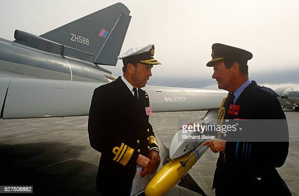 A Royal Navy Admiral and an RAF Air Chief Marshal inspect a missile on the wing tip of a Eurofighter fighter jet VIPs and special military guests...