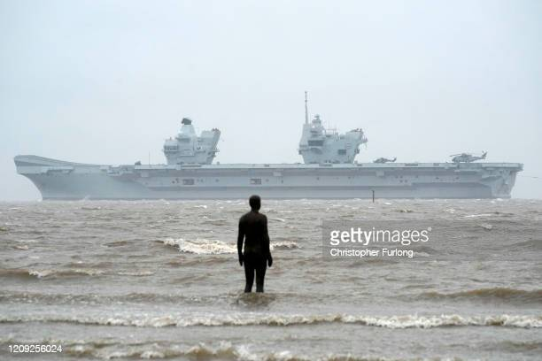 Royal Navy aircraft carrier HMS Prince of Wales sails past the statues of 'Another Place' as it arrives in Liverpool on February 28 2020 in Liverpool...