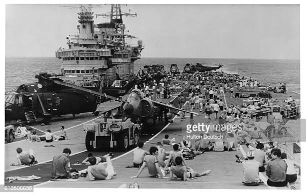Royal Navy crewmen of the HMS Hermes aircraft carrier relax on the flight deck Their task force is headed towards the Argentineoccupied Falkland...