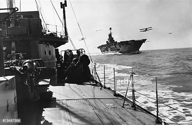 A Royal Navy destroyer accompanies the aircraft carrier HMS Ark Royal on patrol