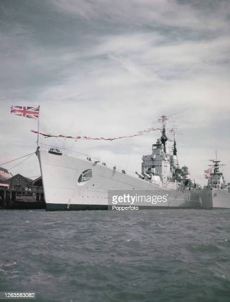 Royal Navy fast battleship HMS Vanguard moored dockside at Her Majesty's Naval Base Portsmouth in Hampshire England in June 1953 Festooned with flags...