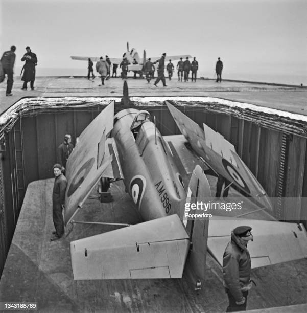 Royal Navy Fleet Air Arm Grumman F4F Wildcat carrier based fighter aircraft, initially named the Martlet by the Royal Navy, is lowered by lift from...