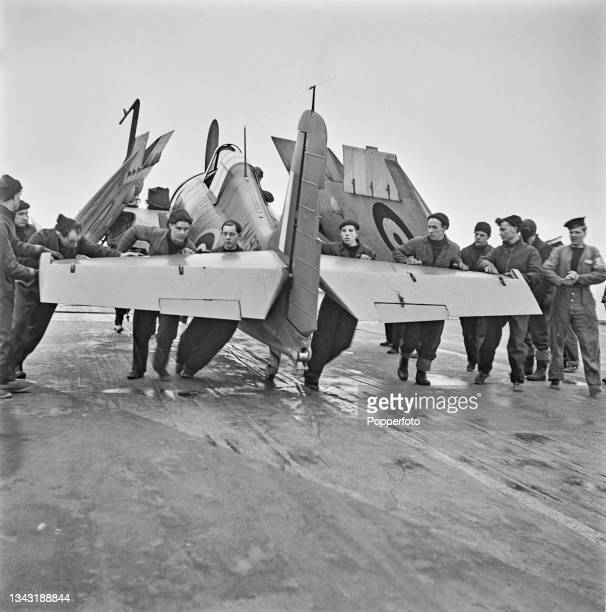 Royal Navy Fleet Air Arm Grumman F4F Wildcat carrier based fighter aircraft, initially named the Martlet by the Royal Navy, is moved to an aircraft...