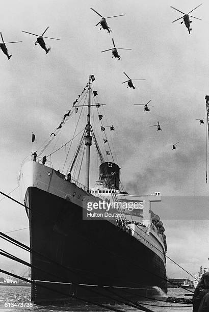 Royal Navy helicopters fly in formation over the Cunard liner Queen Mary as she leaves Southampton on the last voyage of her career