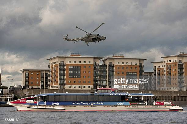 A Royal Navy Lynx helicopter hovers of a passenger ferry on the Thames near Woolwich during a safety and security planning exercise for the London...
