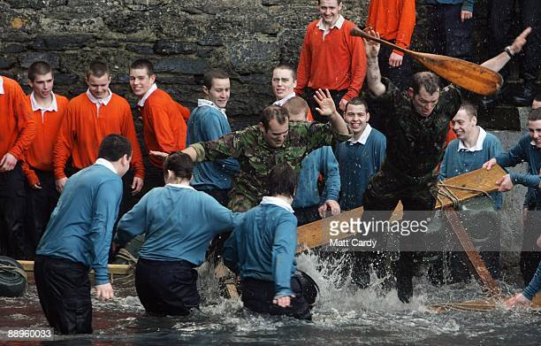 Royal Navy personel jump in the water in the harbour at the Piers Cellars training centre as they take part in team-building exercise close to the...