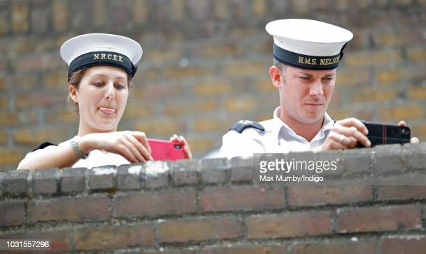 Royal Navy personnel take photographs using their mobile phones as Prince Charles Prince of Wales's visits the newly refurbished 'Maiden' Yacht at...