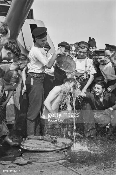 Royal Navy rating is given a shower bath by fellow sailors aboard a Royal Navy destroyer on escort duty with a homeward bound convoy in the North Sea...