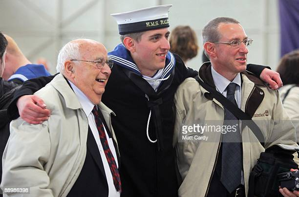 Royal Navy recruit poses for photographs following his passing out parade at the training establishment HMS Raleigh on the final day of their initial...