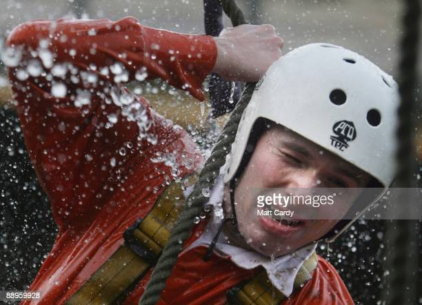 Royal Navy recruit tries to cross a rope ladder ladder above water in the harbour at the Piers Cellars training centre as they take part in...