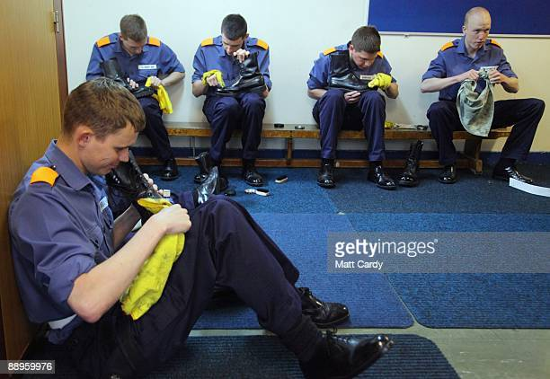 Royal Navy recruits polish their boots in preparation of their passing out parade at the training establishment HMS Raleigh on the final day of their...