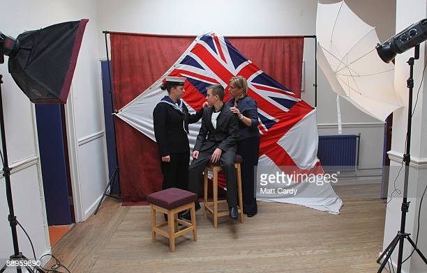 Royal Navy recruits pose for photographs following their passing out parade at the training establishment HMS Raleigh on the final day of their...