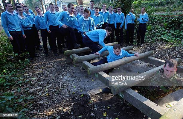 Royal Navy recruits train on the obstacle course at the Piers Cellars training centre as they take part in team-building exercises close to the...