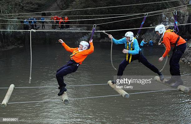 Royal Navy recruits try to cross a rope ladder ladder above water in the harbour at the Piers Cellars training centre as they take part in...