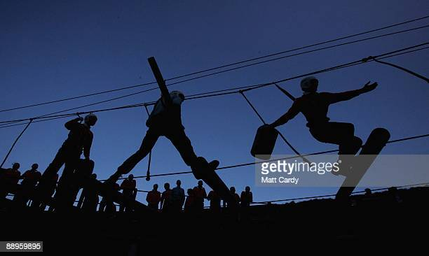 Royal Navy recruits try to cross a rope ladder laden with parts for a raft above water in the harbour at the Piers Cellars training centre as they...