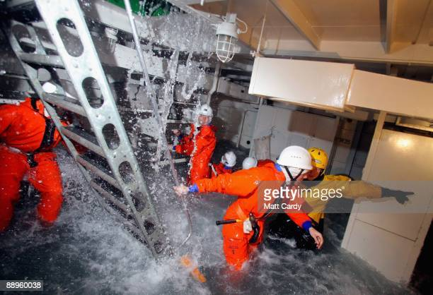 Royal Navy recruits try to stem the flow of flood water in a sinking ship simulator known as a Damage Repair Instructional Unit or HAVOC at the...