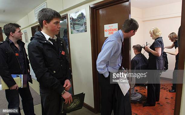 Royal Navy recruits wait for haircuts after they have 'signed on' for service following their arrival at the training establishment HMS Raleigh for...