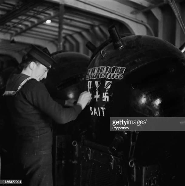 A Royal Navy sailor chalks up a greeting to the enemy on a naval mine in the hold of the former cross channel car ferry MV Princess Victoria during a...