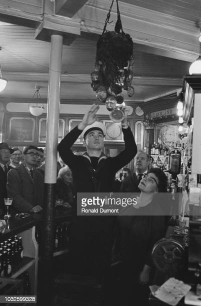 Royal Navy sailor Don Jackson places a hot cross bun in a net above the bar part of an annual Good Friday tradition at The Widow's Son pub in...