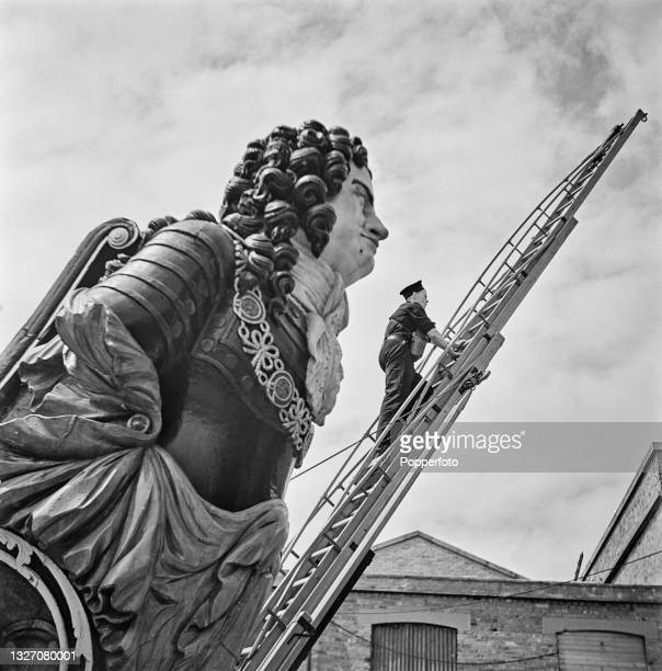 Royal Navy seaman firefighter climbs an escape ladder as part of a firefighting training exercise in Portsmouth, England during World War II in July...