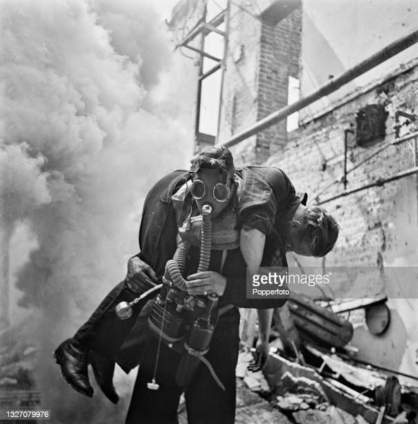 Royal Navy seaman, using a Siebe Gorman Salvus breathing apparatus, carries a colleague to safety from a smoke filled building during a firefighter...
