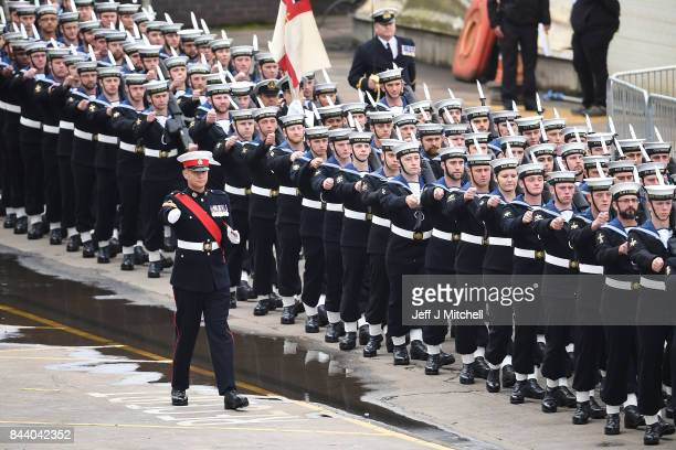Royal Navy servicemen march past HMS Prince of Wales before a naming ceremony for the aircraft carrier at Rosyth Dockyard on September 8 2017 in...