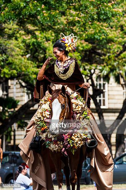 Royal Queen representing one of the Hawaiian Islands riding a horse in the King Kamehameha Floral Parade in Honolulu Hawaii on the Island of Oahu The...