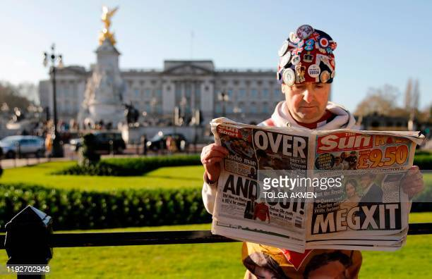 Royal super fan John Loughery holds a copy of a British newspaper as he poses for the media outside of Buckingham Palace in London on January 9...