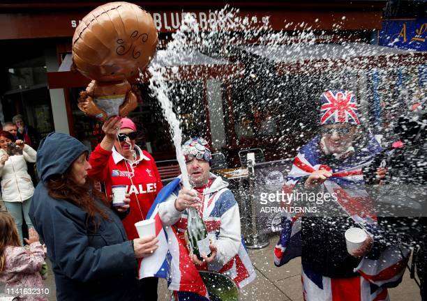 Royal super fans John Loughery pops the cork on a bottle of champagne as they stand near Windsor Castle in Windsor west of London on May 6 following...